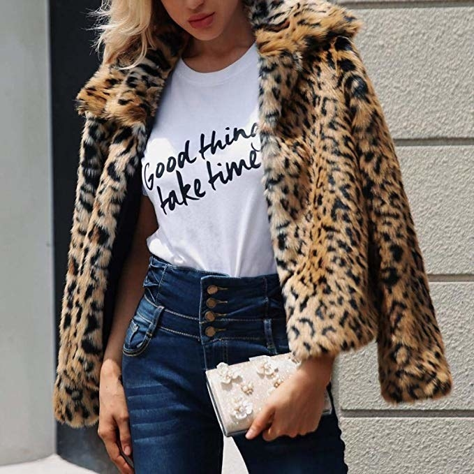 model in jeans and a T-shirt wearing the cheetah print faux-fur jacket on their shoulders