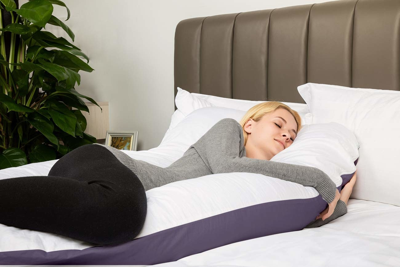 person leaning up against a body pillow that goes underneath the head with a portion that's long either side