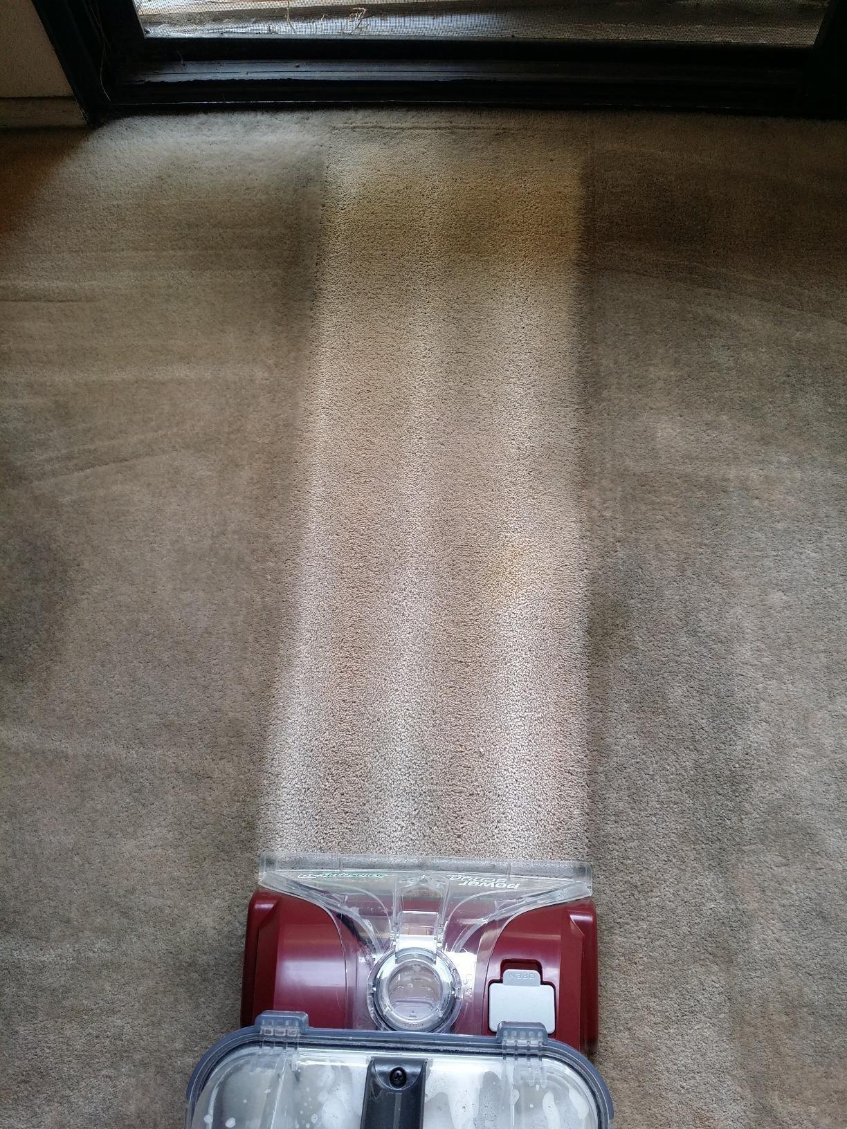 vacuum cleans a light stripe in dark dirty carpet