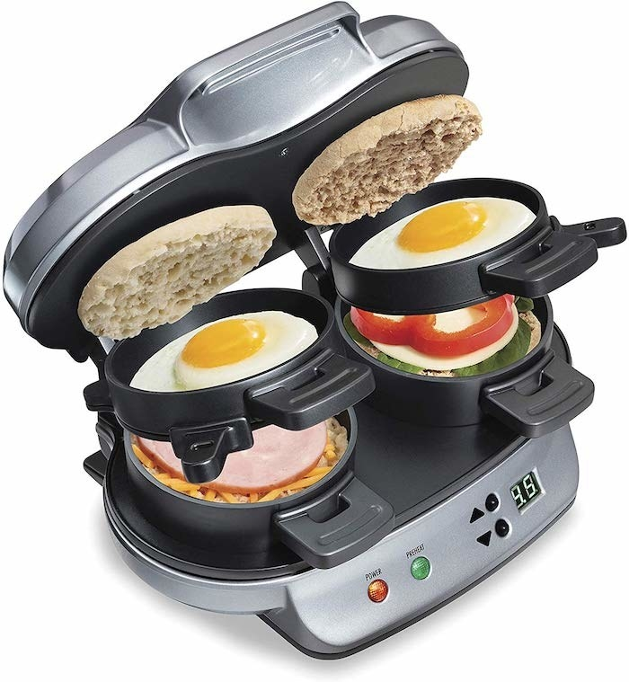 the device which has two sides for two sandwiches and different trays for the bun, a fried egg, meat, and cheese