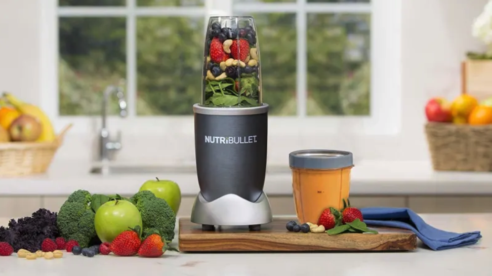 The blender sitting on a counter with unblended ingredients inside of it including strawberries, blueberries, spinach, and nuts