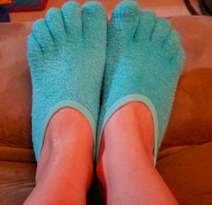 Blue moisturizing socks on reviewer's feet