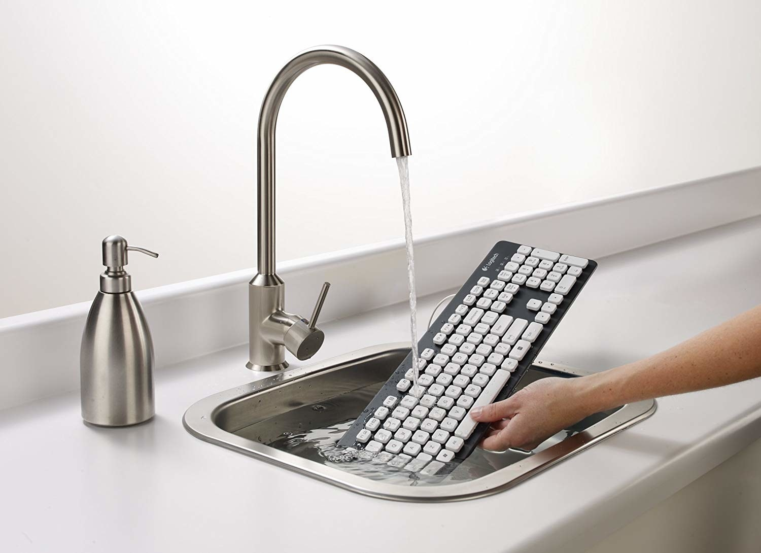 keyboard being hand washed in a sink