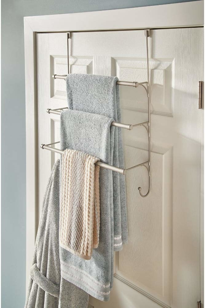 back of bathroom door with a towel rack that has three tiers of racks for towels