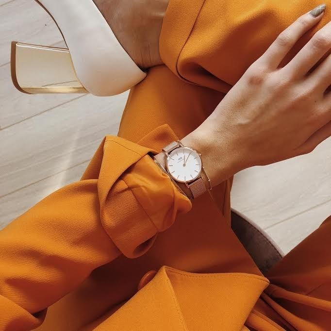 model wearing gold watch with white face