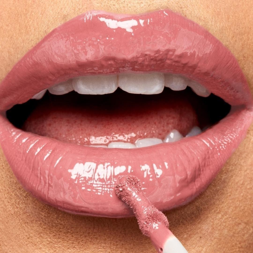 Model applying the lip gloss in pink