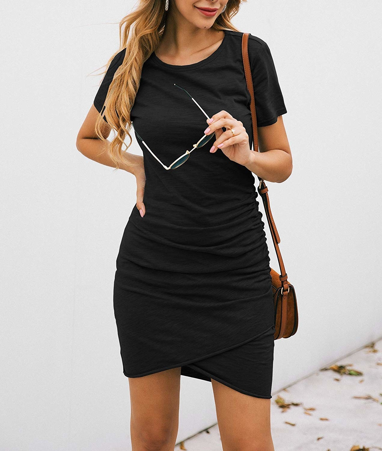 A model showing the black mini dress worn with a crossbody bag and sunglasses