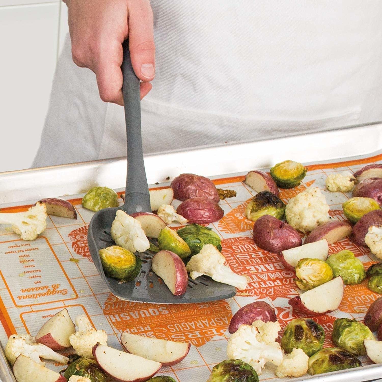 The veggie turner gathering vegetables from a baking sheet