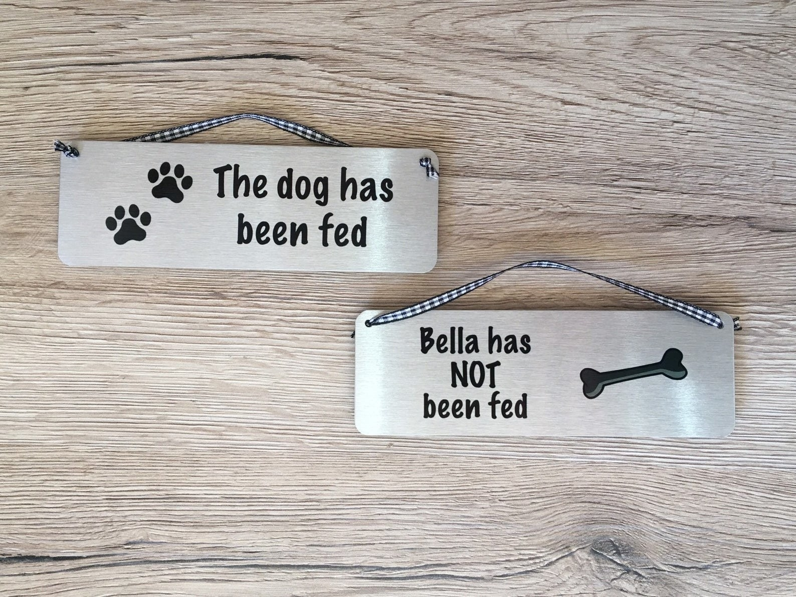 """a dog tag with a tiny rope for hanging at the top. One side says """"the dog has been fed."""" Another tag shows what the other side can say which is, """"Bella has NOT been fed."""""""