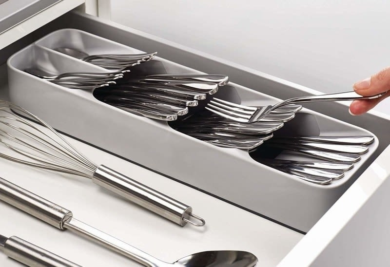 A person putting a fork into the gray cutlery organizer inside of a drawer