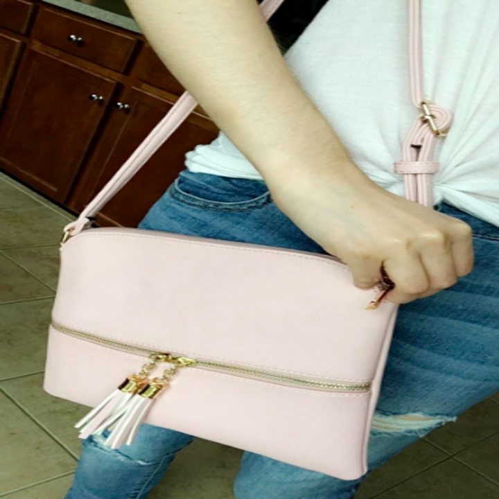 A reviewer carrying the bag in pale pink with a tassel zipper detail