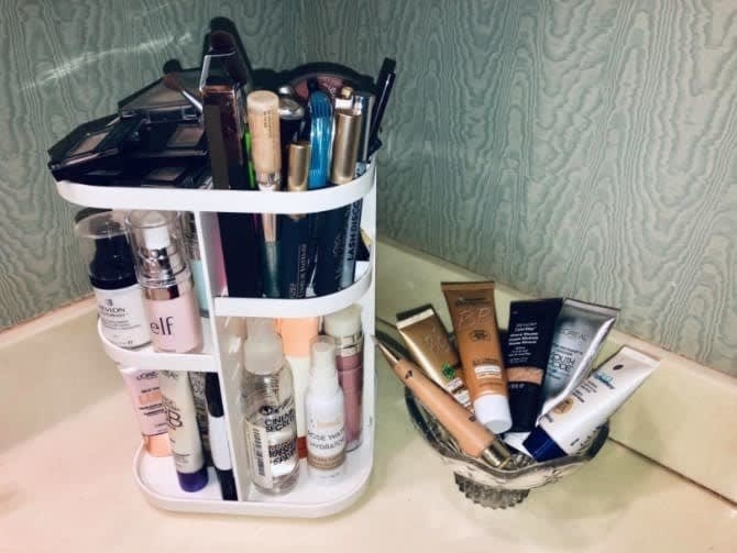 A reviewer photo of the white organizer holding numerous makeup products