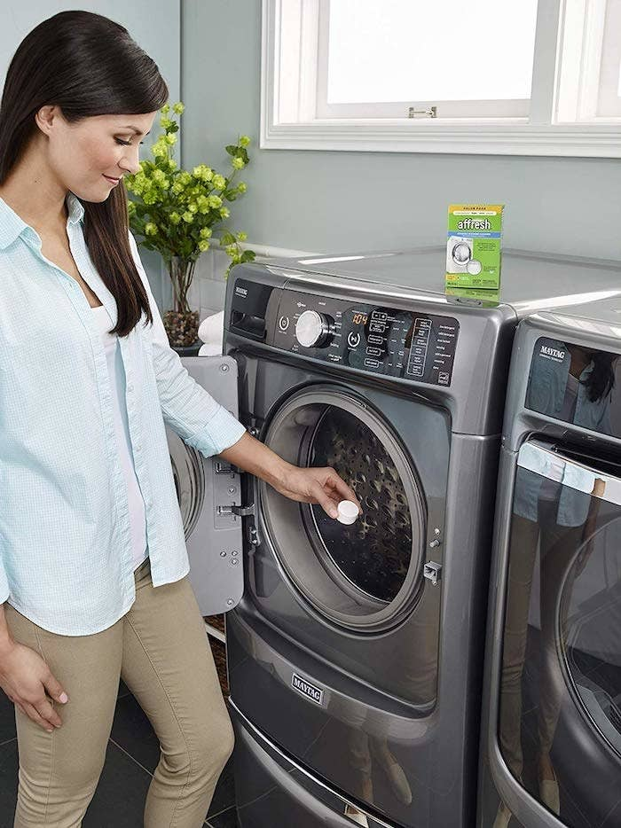 Product photo showing a model place Affresh washing machine tablets into their washing machine