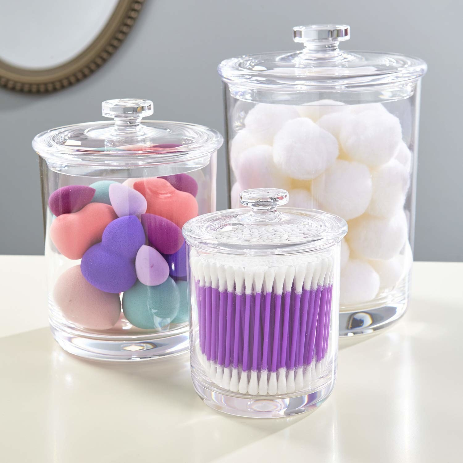 three glass canisters in different sizes holding various beauty products