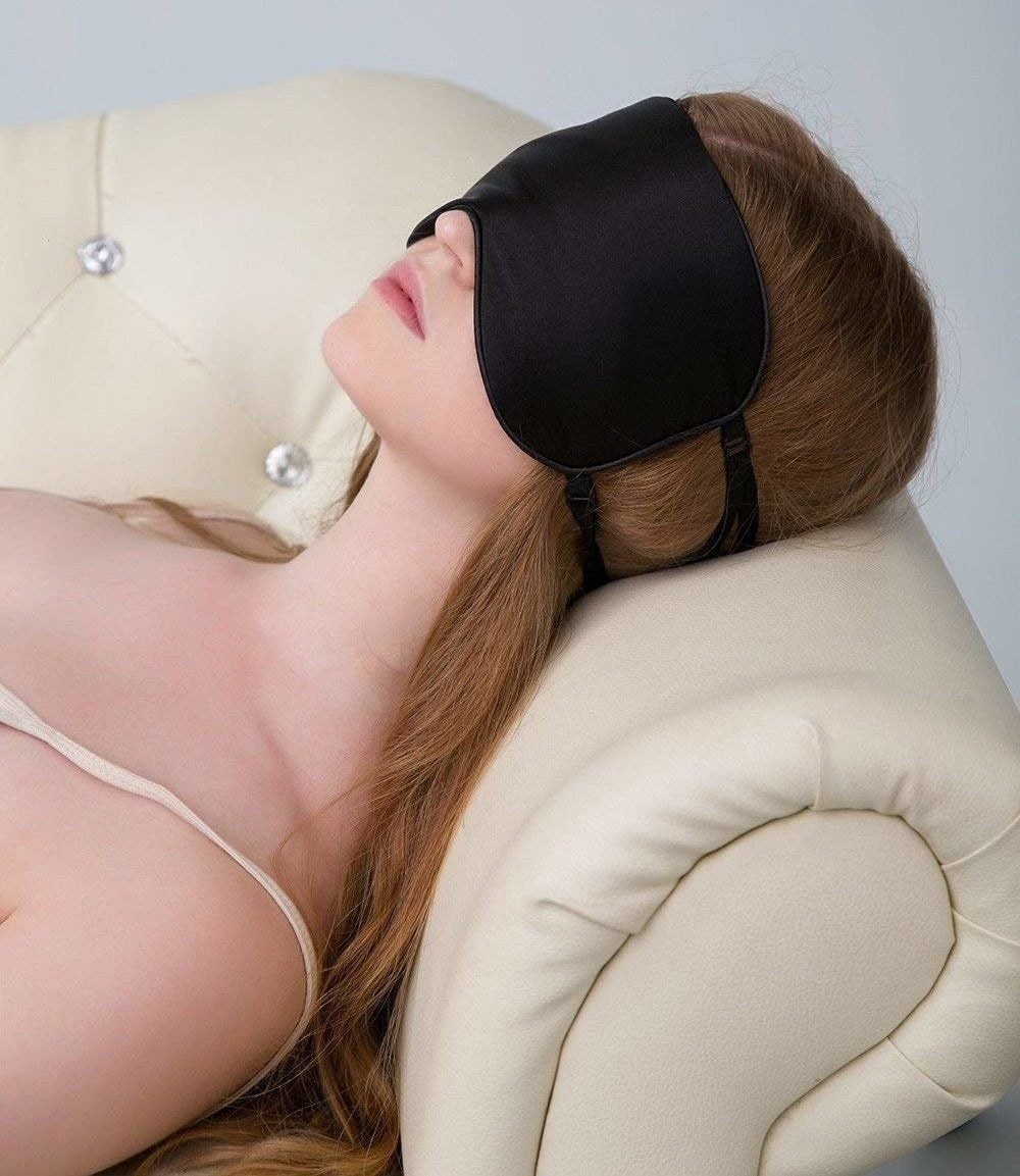 a woman laying on the couch with an eye mask over her face