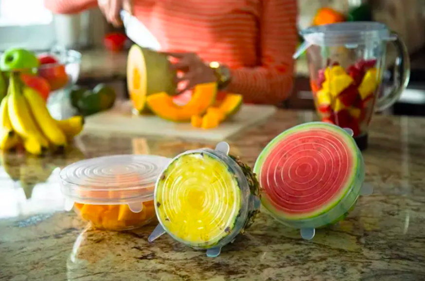 Bowl of fruit, half pineapple, and half watermelon all covered with adjustable lids