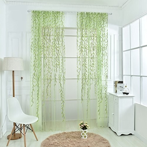 The sheer drapes with what looks like green vines running down either side on a window