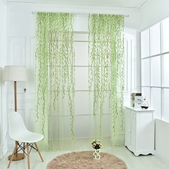 The sheer drapes with green vines going down them hanging across the full-length window