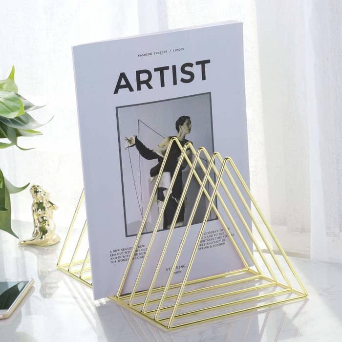 Triangular brass magazine rack
