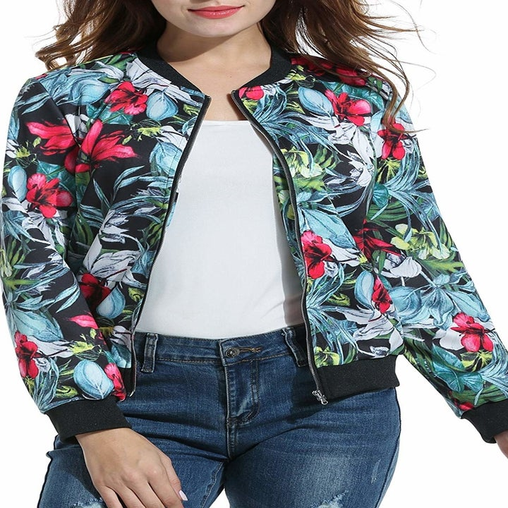 A model in a black, blue, green, and pink tropical print bomber