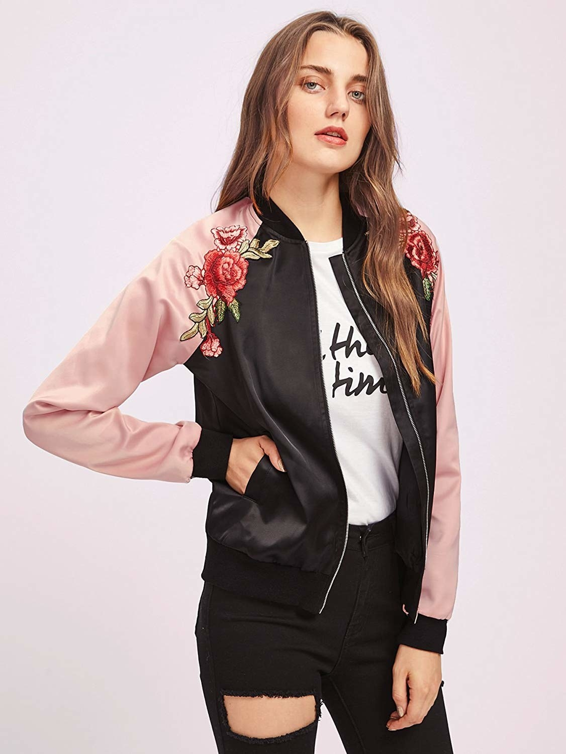 A model wearing the pink and black bomber with rose embroidery