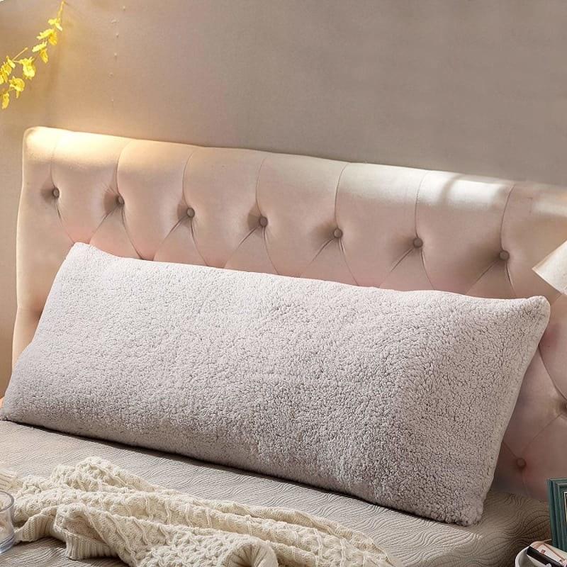 Rectangular body pillow with a fuzzy cover in beige on a bed.