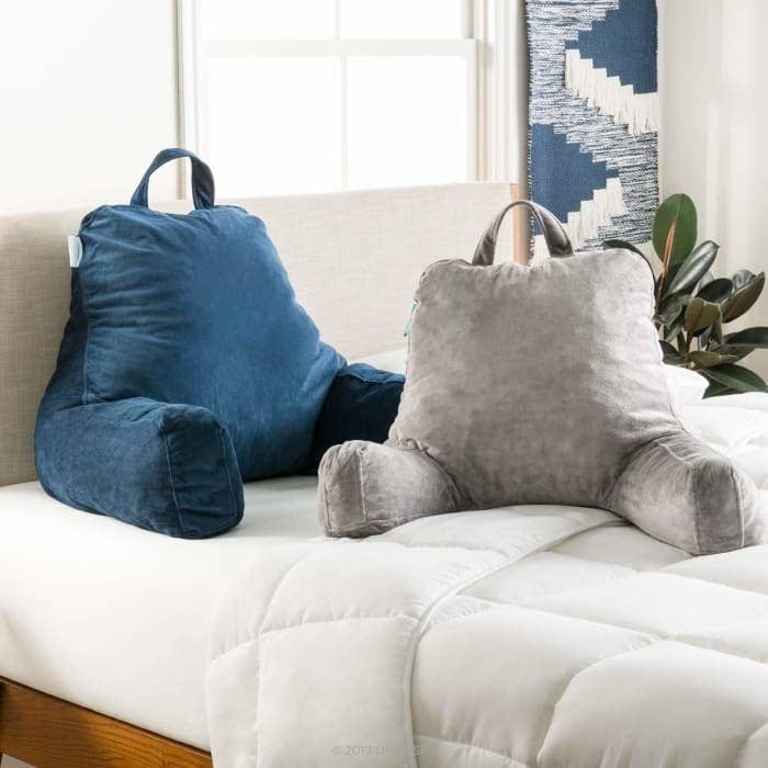 A blue and grey stand up pillow with arms and a handle on the top.