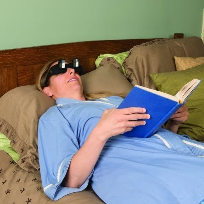 Model lying horizontally with a book in their hands and the black glasses on, making it easy for them to read the book without straining their neck