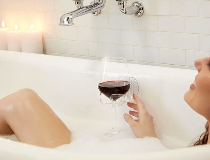 Model in a bubble bath with the clear holder suctioned to the side of the tub with a glass of red wine in it.