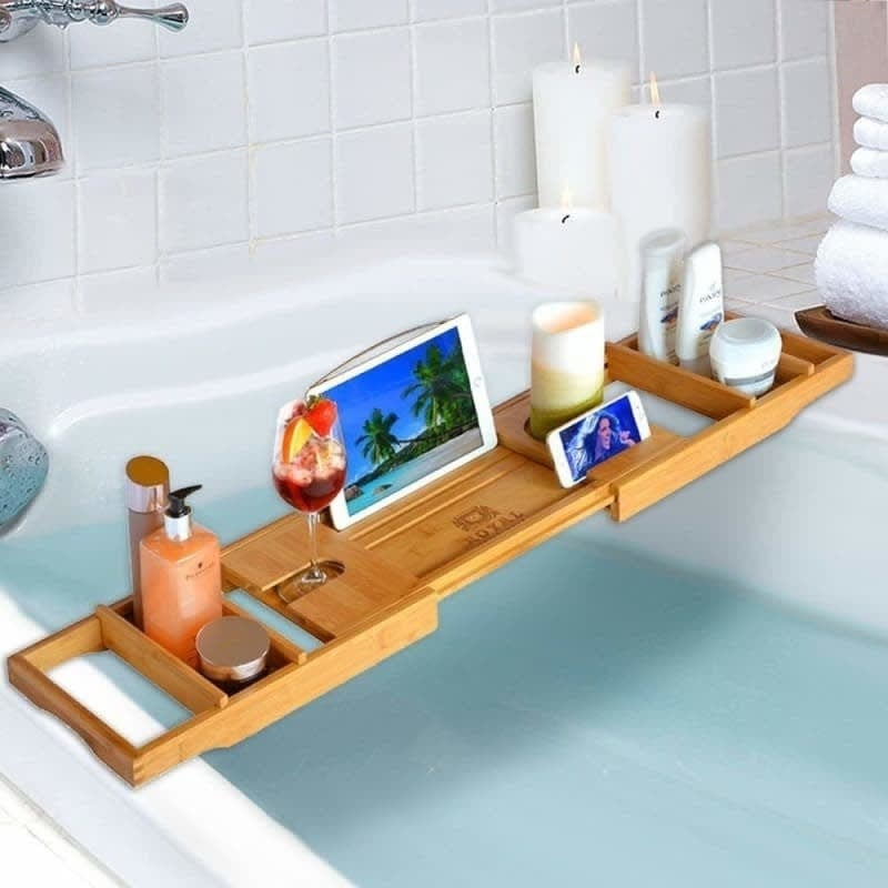 A wood tray over a bathtub with a tablet holder, wine glass slot, and two removable trays for other accessories.