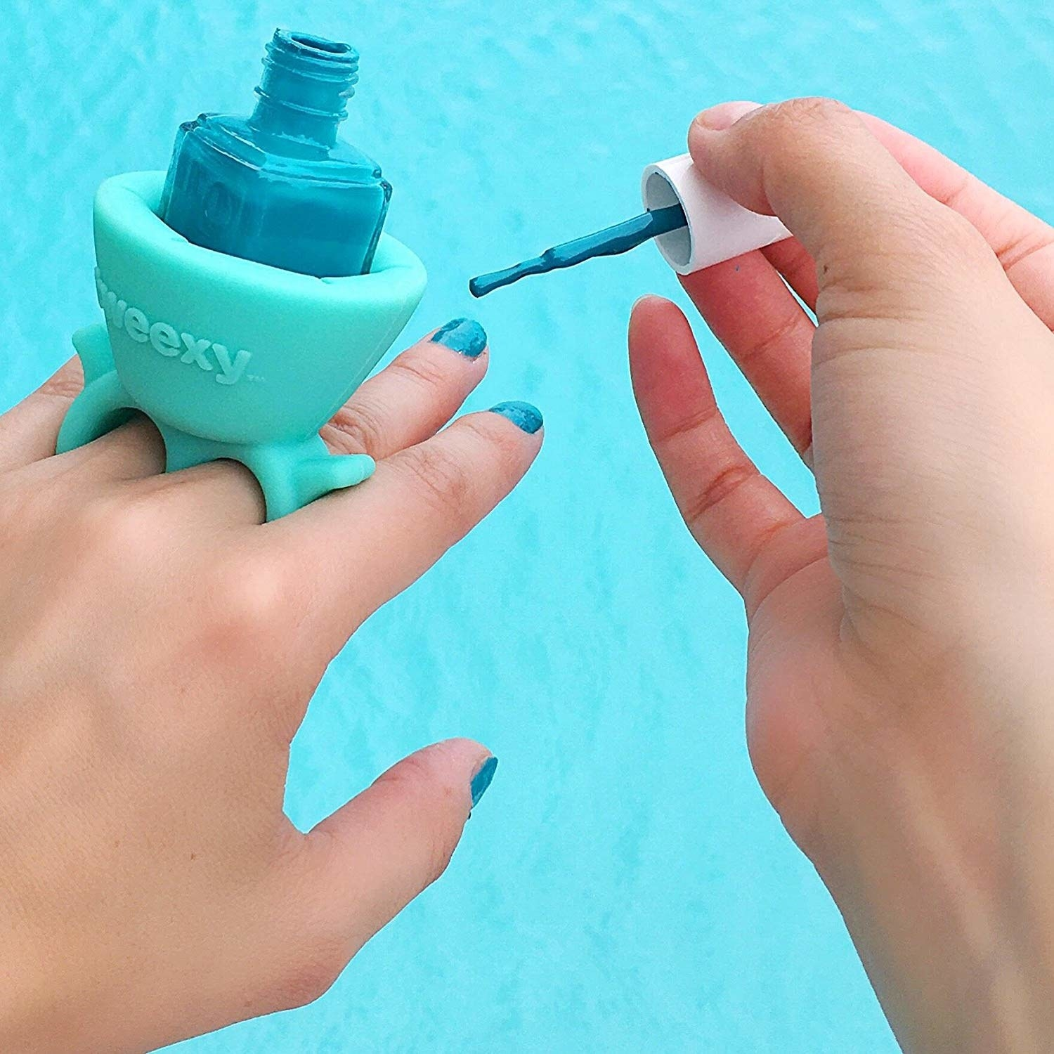 Model's hands with the Tweexy on the left hand. It has two rings and a holder on top with a bottle of nail polish in it to keep it steady. The right hand is holding the nail polish brush and painting the left hand's nails