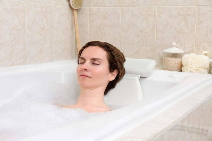 Model in a bathtub with a white pillow with a rectangle part on the edge of the tub and circular part on the inside of the tub.