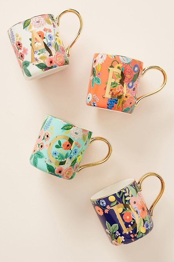 Four coffee mugs with different colored floral patterns on them, gold handles, and gold initials on the front.