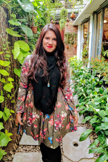 A reviewer wearing the dress in olive green
