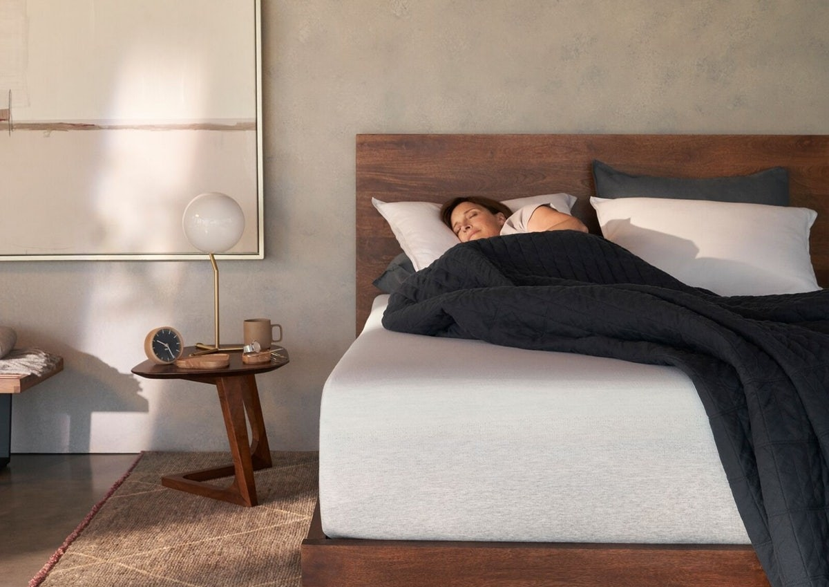 The white thick mattress with a model sleeping on top of it in a bedroom.