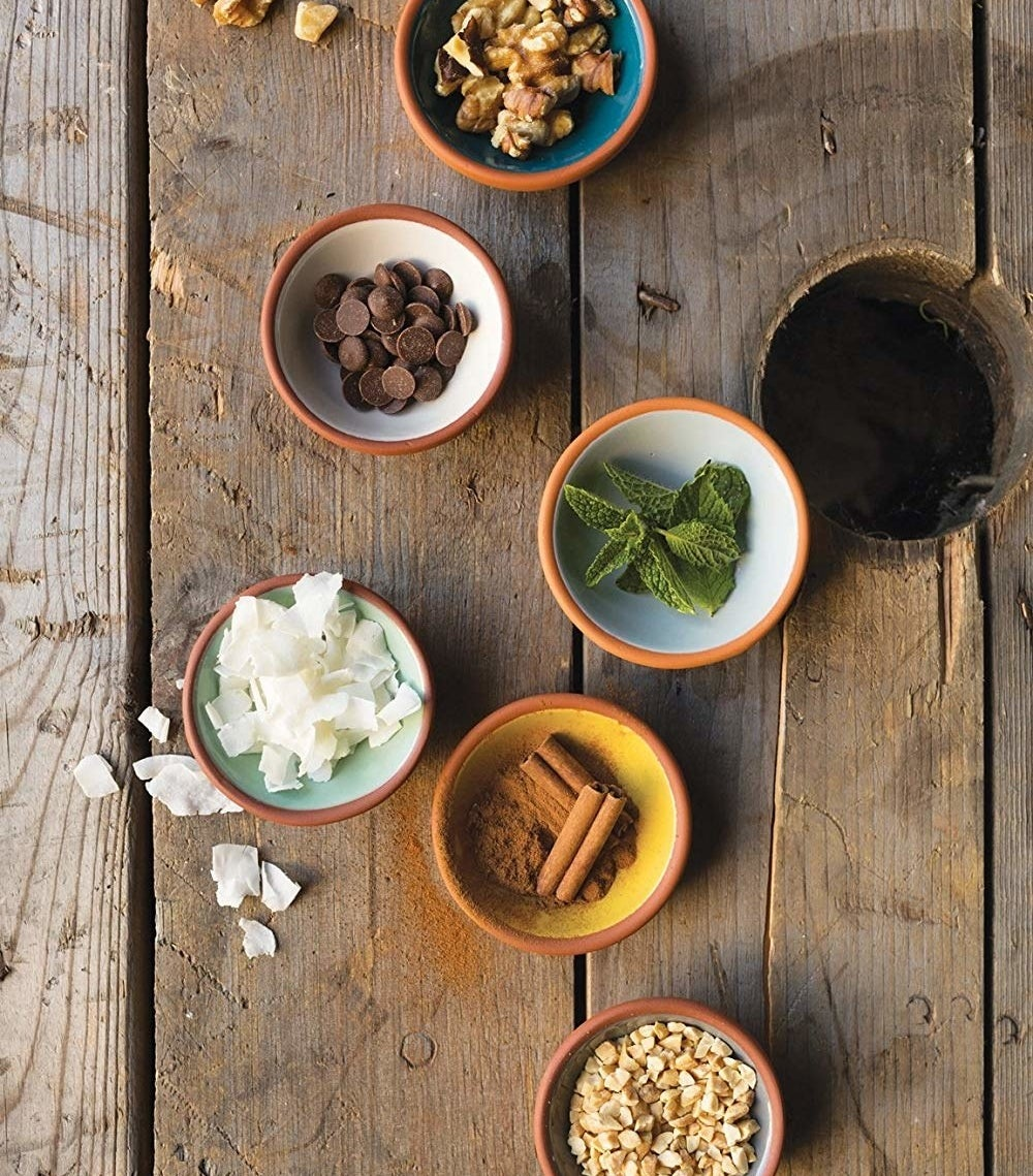A set of terracotta pinch bowls with various spices and ingredients inside of them