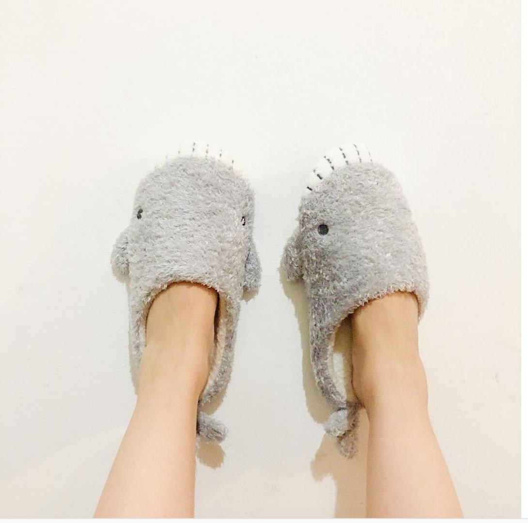 Reviewer pic of their feet in the grey fuzzy slippers that look like sharks with eyes, teeth, and a tail on the back