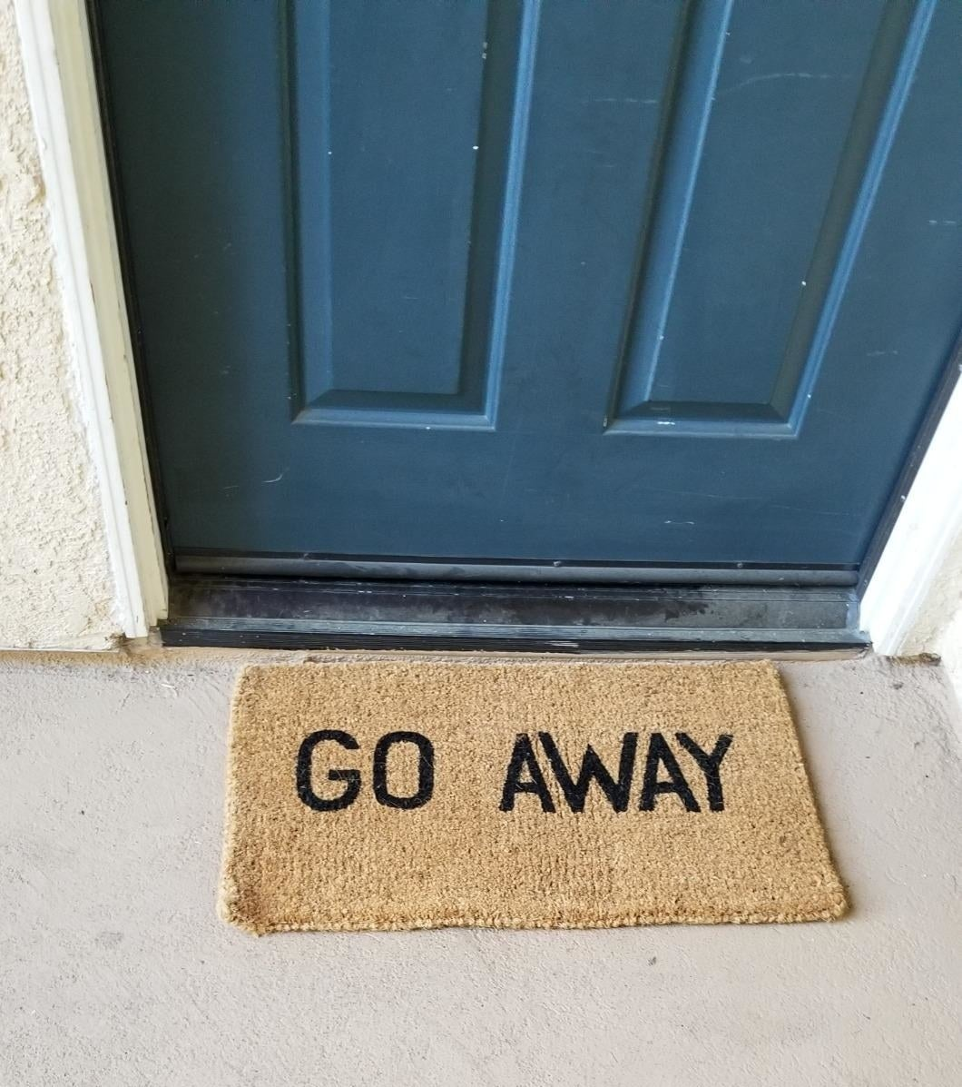 "Reviewer pic of a brown doormat with the words ""Go Away"" written on it."