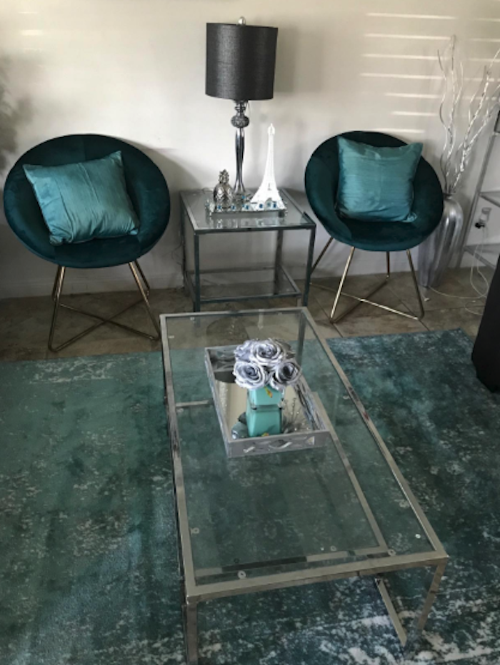 two circular-shaped velvet accent chairs in green with green pillows and a lighter green and white rug