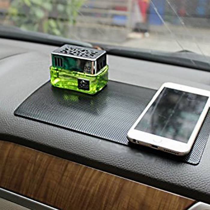 A sticky mat attached to the car dashboard with a cell phone lying on it