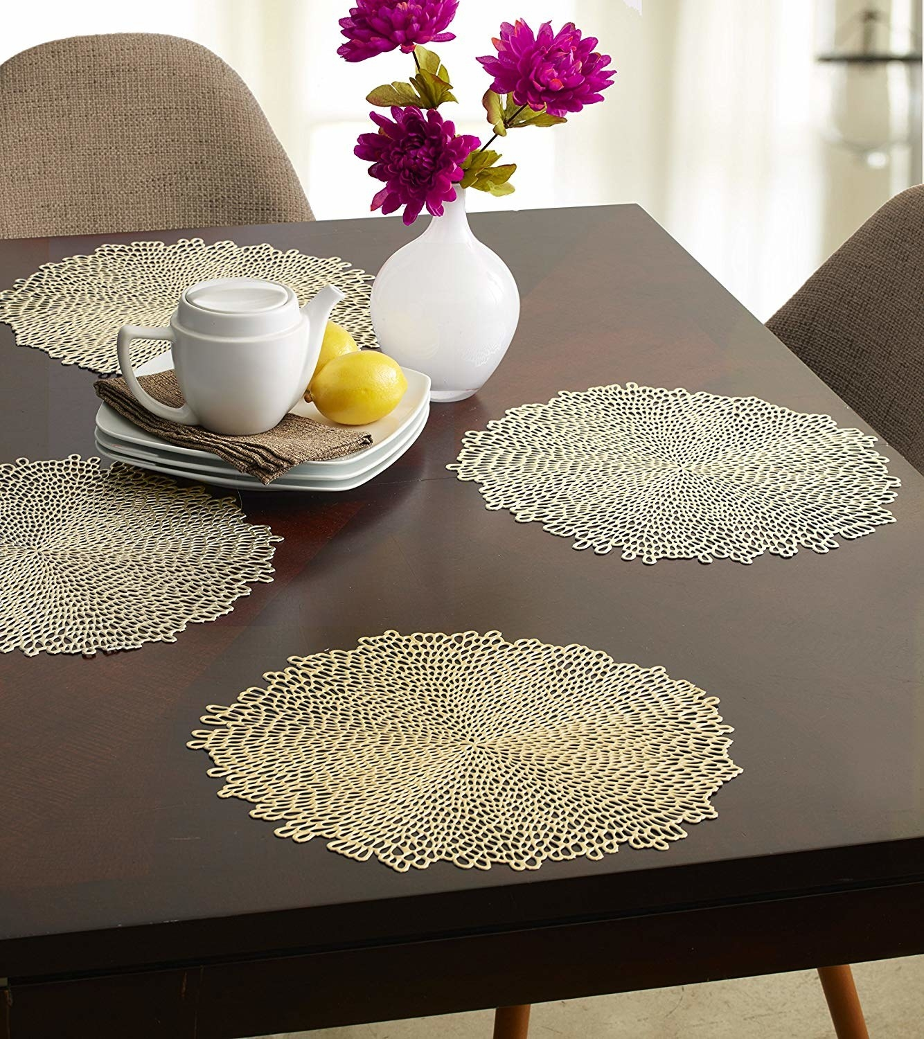 Four metallic placemats on a table with a vase of flowers and dinnerware