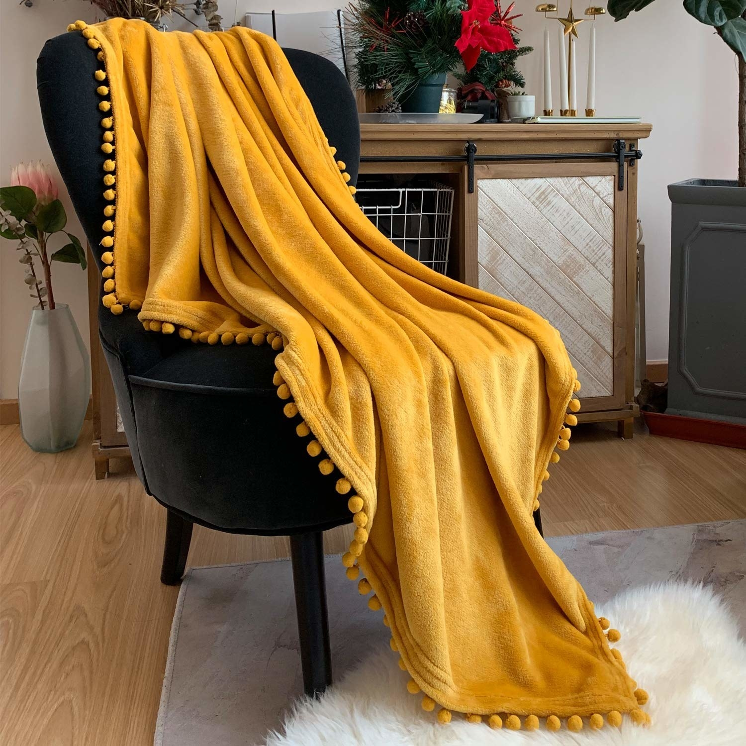 the yellow throw blanket with a pompom trim