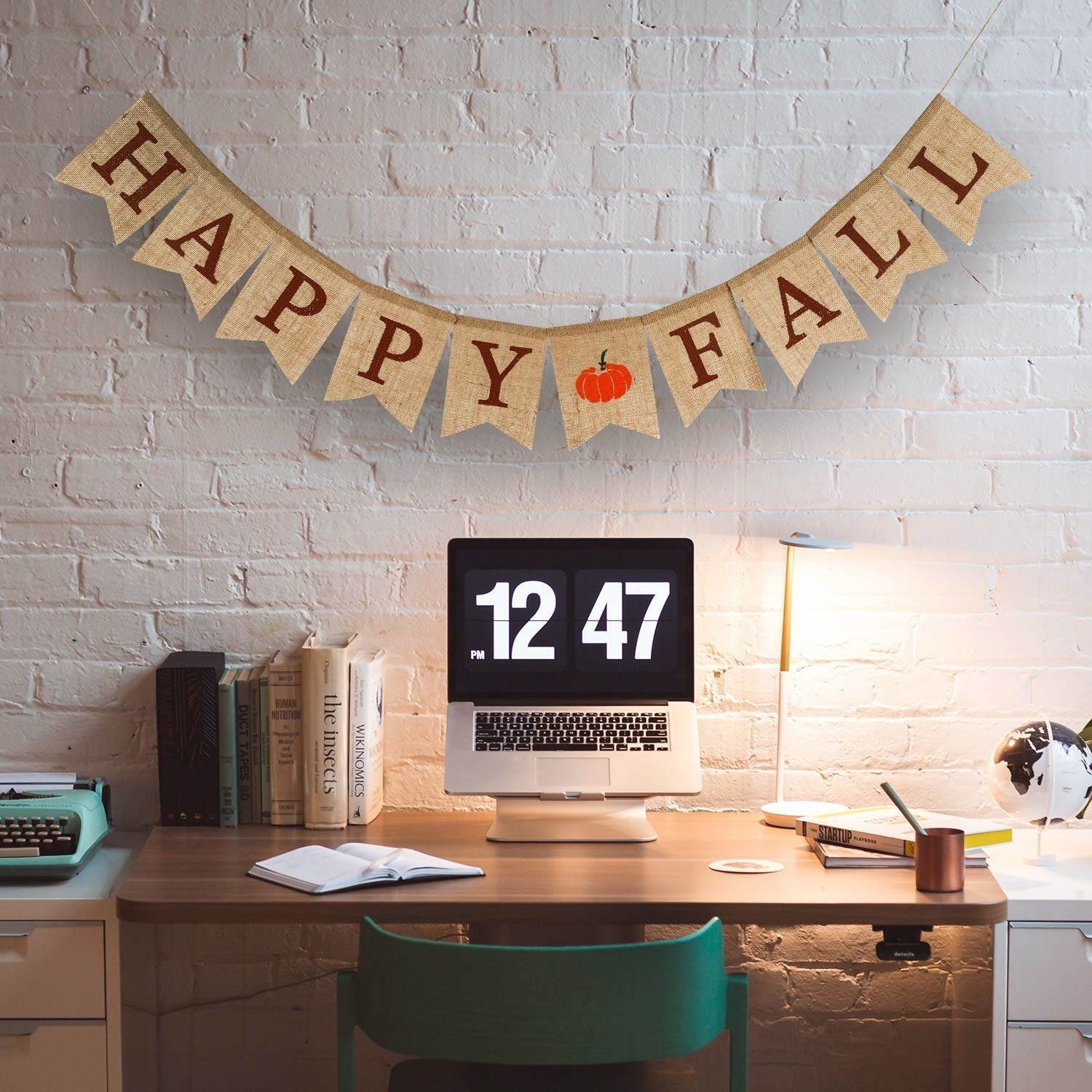 """The natural burlap banner says """"Happy Fall"""" with a pumpkin between the two words"""