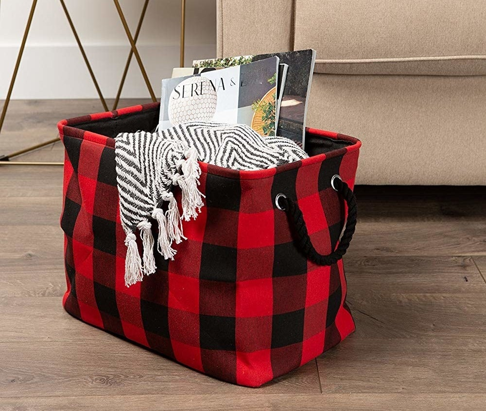 The black and red plaid storage bin filled with a blanket and magazines
