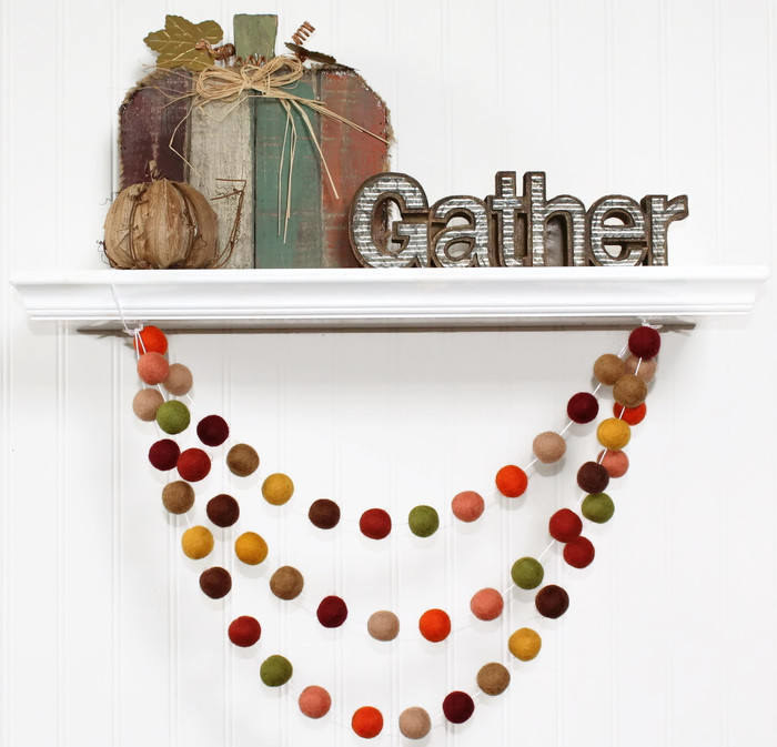 The garland has felt balls in shades of green, red, brown, and yellow