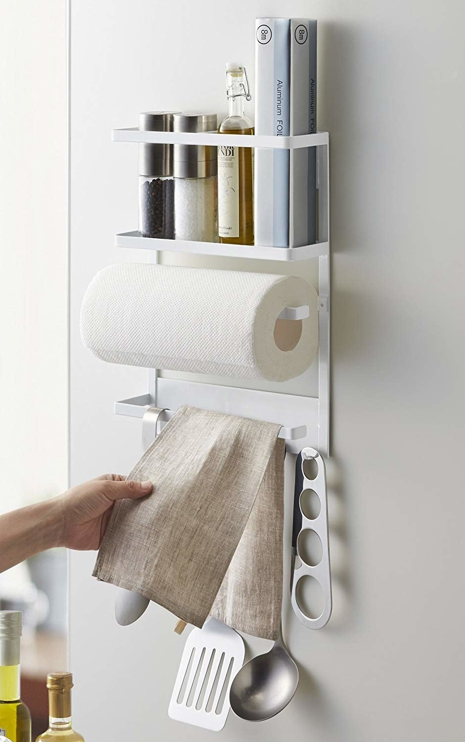 organizer on side of a fridge holding a paper towel roll, salt, pepper, and oil on a top rack, and a towel and cooking utensils hanging from hooks on the bottom