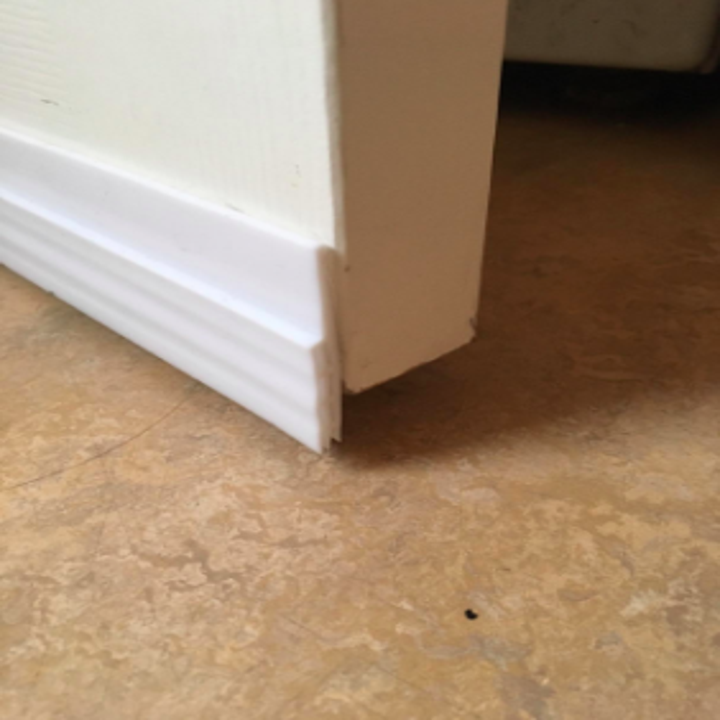 reviewer's close up of white door draft stopper on the bottom of the door