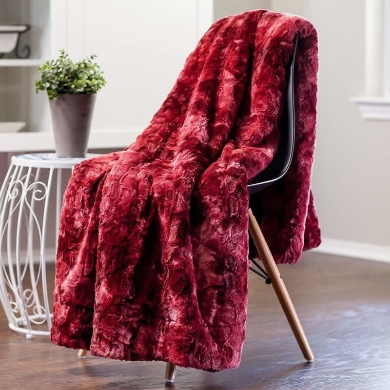 A red faux-fur blanket is draped entirely over a chair.