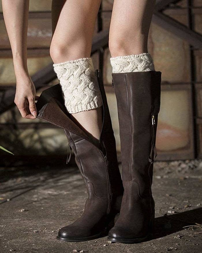 model wearing boot cuffs unzipping boot to reveal knitted tube about six inches long around calf