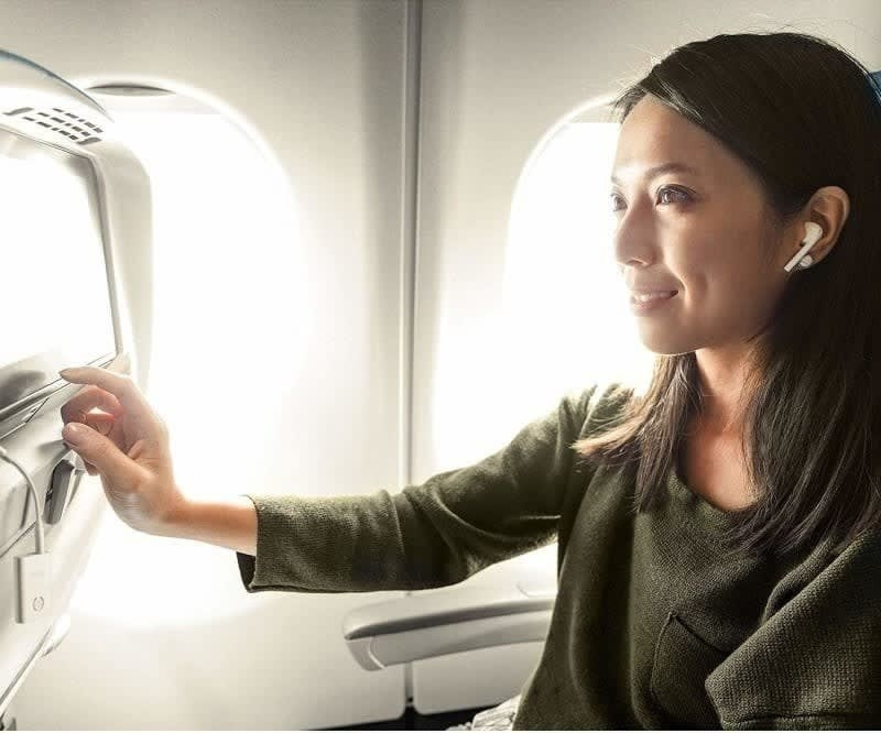 model with wireless ear buds in with the small white Airfly connected to the screen on the back of the chair on an airplane, showing how it connects the two